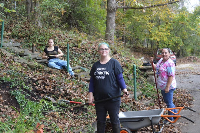 Students Heidi Slater, front, and Chelsey Horton, back left, and teacher's aide Mindy Graham, far right, help clean up the walkways outside Hart House during Service Day.