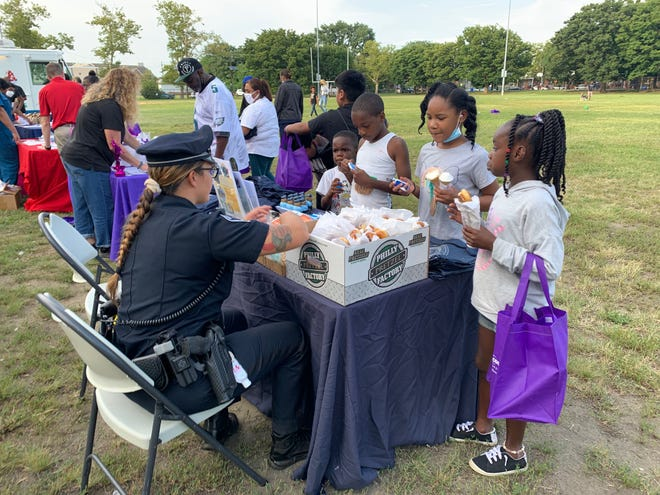 A Camden County policewoman shares soft pretzels with Branch Village families in Camden on National Night Out in August. Better Tomorrows has been awarded a $5,000 grant to promote better relations between police and residents in affordable housing like Branch Village.
