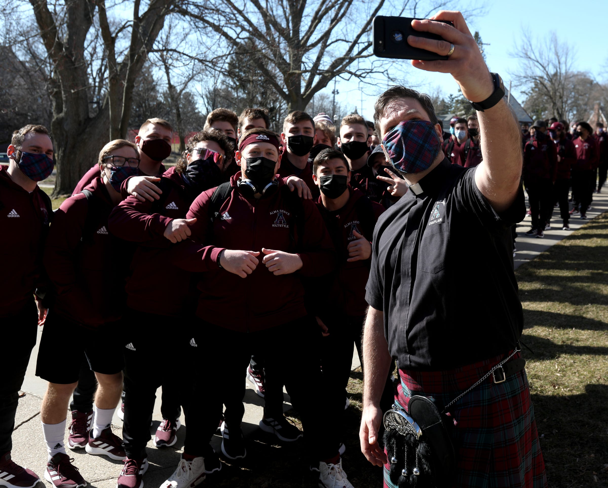 Andrew Pomerville, the Alma College chaplain, wanted a selfie with some members of the Alma football team before they marched off in line following bagpipes to the football field for their game against Adrian College in Alma, Michigan, on Saturday, March 20, 2021.