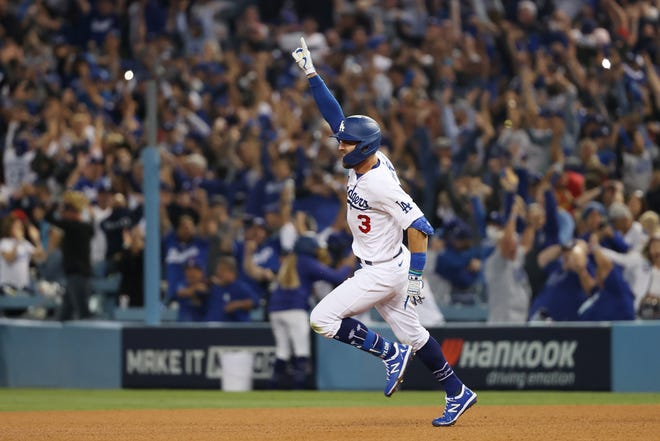 The Dodgers' Chris Taylor celebrates his walk off two-run home run in the ninth inning to defeat the St. Louis Cardinals, 3-1, in the NL wild-card game Wednesday in Los Angeles.