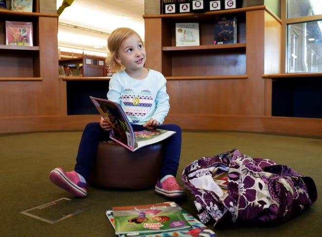 Lenni Marto, 3, of Pulaski looks at books while visiting the Brown County Library's Weyers-Hilliard Branch on Oct. 6, 2021, in Howard, Wis.