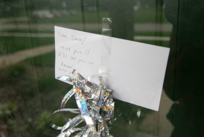 A note is taped to the storm door of a murder victim in Genoa Township, shown Thursday, Oct. 7, 2021.