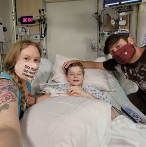 Logan Bouvier, 11, with his parents Jessica and Chris Bouvier at Sparrow Hospital. Logan spent two weeks in the hospital's pediatric intensive care unit. Doctors don't know if he had multisystem inflammatory syndrome, a rare condition associated with COVID-19.