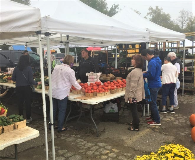 Customers purchase fruits and vegetables from the Mark Prielipp Greenhouse & Mohr stand.