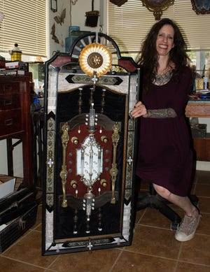 Artist Wendy Gadzuk poses with an assemblage piece she made using medical waste Oct. 6 in her Morongo Valley studio.