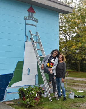 Rose Lucas Haninger, left, and Jennifer Collins spent most of Wednesday painting the new mural of the Marblehead Lighthouse on the building at Radar Park. The ladies will continue to work on the mural as weather allows.