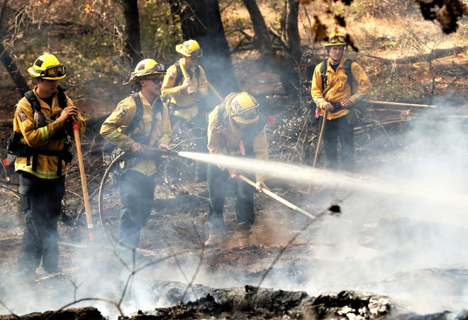 Firefighters extinguish hot spots from a vegetation fire that started Thursday between Shasta Lake and Mountain Gate west of Interstate 5.
