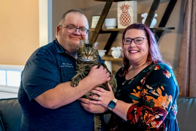 Brian and Courtney Merce pose with their cat Susie Q in their Zanesville home. They are celebrating five months since Brian, a Tri-Valley High School teacher, received a kidney transplant.