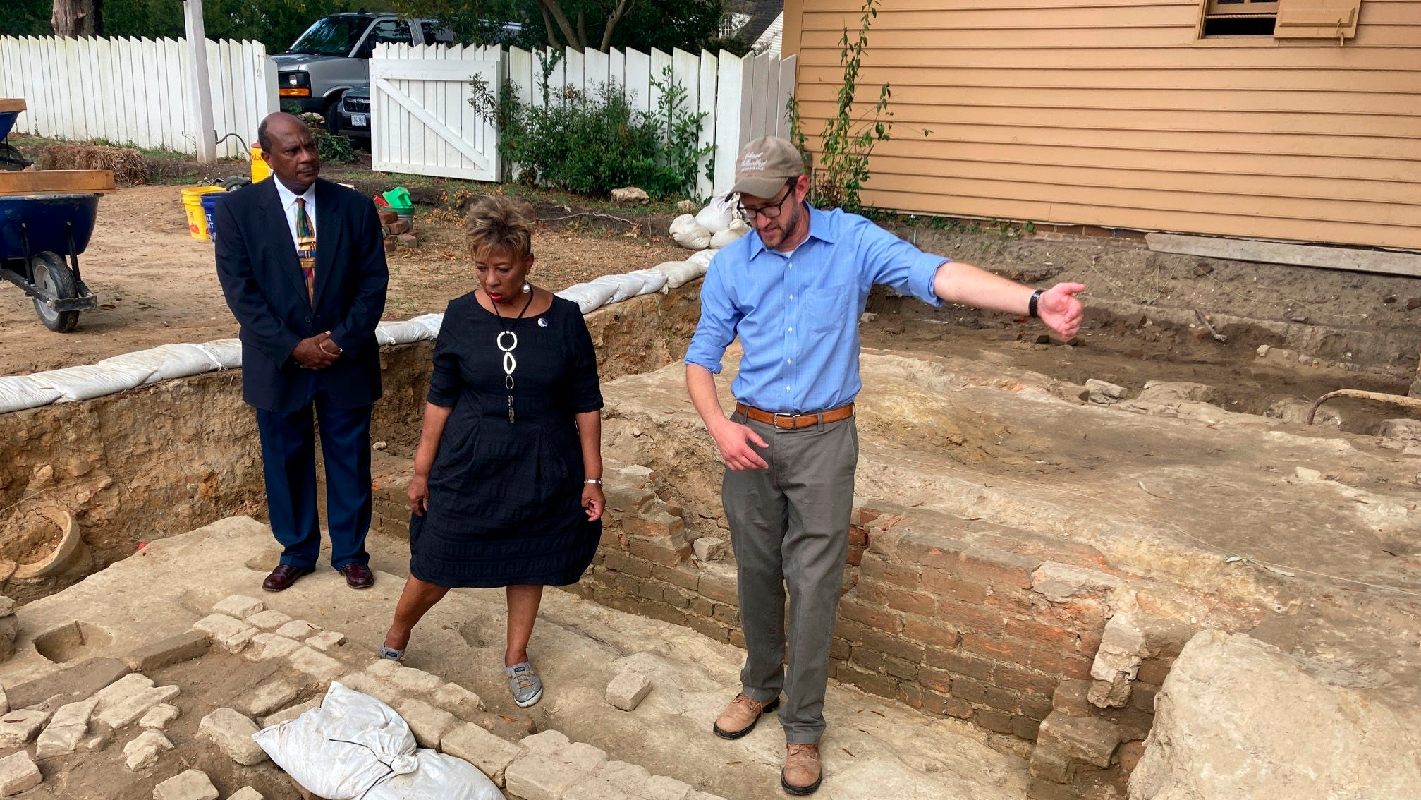 Reginald F. Davis, from left, pastor of First Baptist Church in Williamsburg, Connie Matthews Harshaw, a member of First Baptist, and Jack Gary, Colonial Williamsburg's director of archaeology, stand at the brick-and-mortar foundation of one the oldest Black churches in the U.S. on Wednesday in Williamsburg, Va.