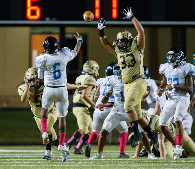 Northeast quarterback JT Thomas throws a pass that is tipped by Crockett's Caleb Dickey (33) and intercepted in the end zone by Cougars defensive back Xavier Chapa during the Cougars' 21-13 win Thursday at Burger Stadium.