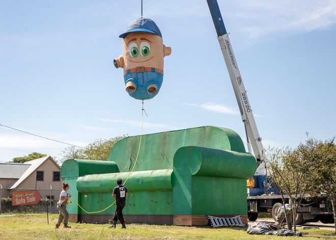 Travis, the last of the famous Austin couch potatoes, is lifted from his longtime resting place on a 34-foot-long sofa at Austin's Couch Potatoes furniture store on Interstate 35 in North Austin on Friday. He and the other two couch potatoes, each weighing 2,000 pounds, are moving to a new home at Circuit of the Americas.