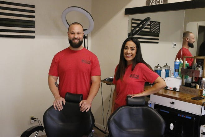 Zach Arduini and Erica Monroe prepare to open Stay Blessed Barbershop in Brownwood on a recent morning.