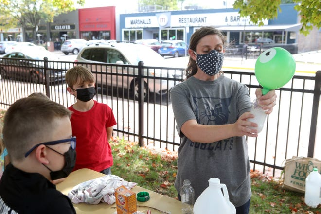 Third-graders Simon Borkowski (foreground) and Winston Bellay look on as parent volunteer Megan Duffy-Johnson demonstrates how mixing baking soda and vinegar reacts by creating a gas during Stevenson Elementary School's All Science Day program Oct. 6 at Pierce Field. Nine stations with science-related demonstrations and activities were led by community members.