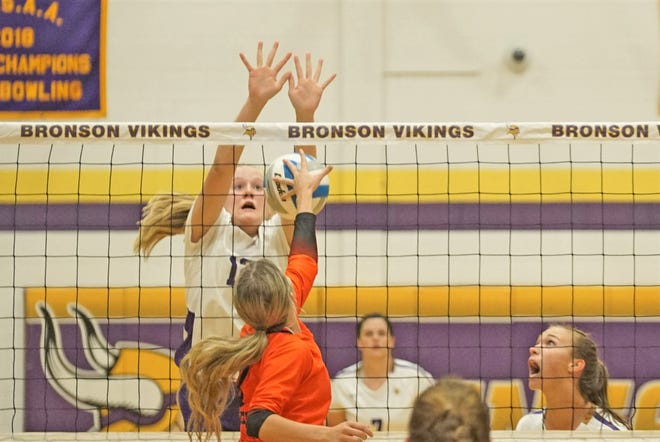 Bronson freshman Payton Springstead looks for a block while teammate Karissa Gest calls out directions.