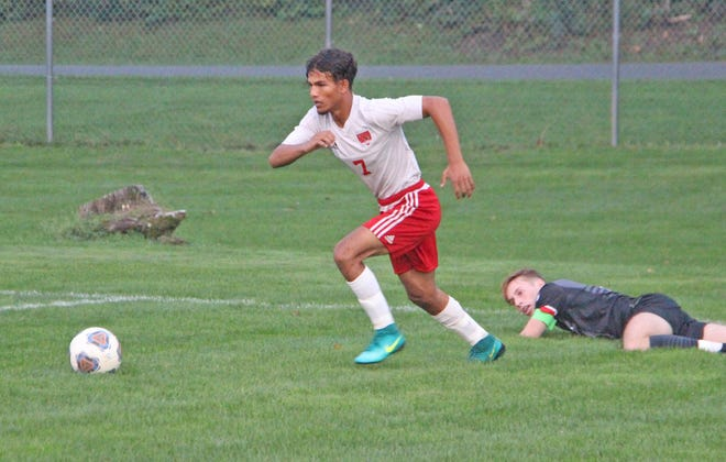Coldwater's Ahmed Omar (7) leaves a Marshall defender in the mud Thursday night