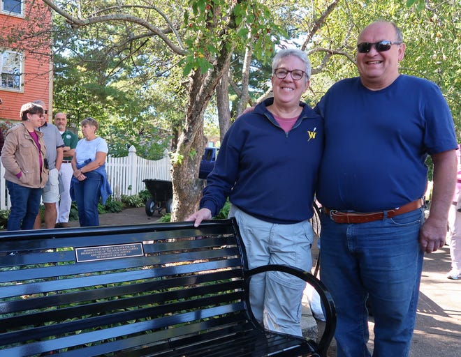 Beth Fischer with Dover Mayor Robert Carrier after the surprise unveiling of a bench dedicated to Fischer for her volunteer work for the city.