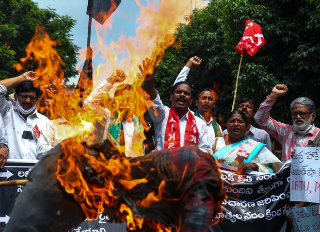 Indian farmers protesting against the killing of four farmers in Uttar Pradesh state after being run over by a car owned by India's junior Home Minister Ajay Mishra burn an effigy of the federal government in Hyderabad, India, Monday, Oct. 4, 2021.