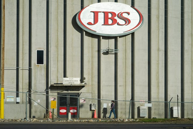 In this Oct. 12, 2020 file photo, a worker heads into the JBS meatpacking plant in Greeley, Colo. Meatpacker JBS Foods Inc. faces about $59,000 in fines after a worker fell into vat of chemicals used to process animal hides and died at one of the company's meat processing facilities in northern Colorado, officials said.