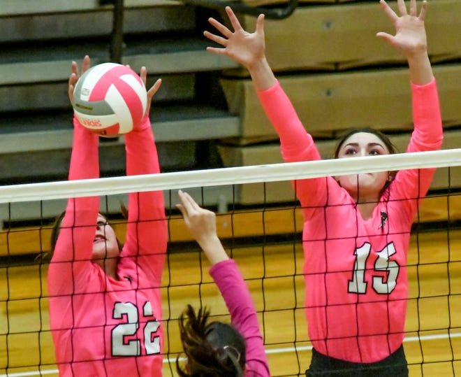 Garden City High School's MiKayla Martinez, left, knocks a Ulysses shot down on to the Tigers' side of the net for a point as she and teammate Mackenzie Lucas go up for a block Thursday during a match in a volleyball triangular at GCHS.
