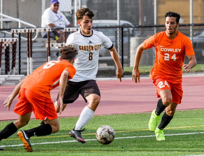 Garden City Community College's Luis Milan dribbles the ball between a pair of Colwley County defenders during a September game at Broncbuster Stadium.