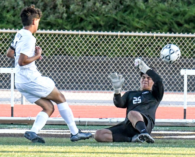 Garden City High School goalkeeper Jonathan Hernandez, right, knocks the ball away from the goal off a shot by Wichita Heights' Oscar Vitela Monday at Buffalo Stadium.