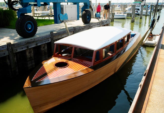 One of Grand Craft's handmade mahogany boats being lowered into the water. The company recently announced it has moved from Holland to Genoa City, Wisconsin.