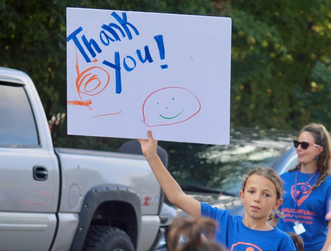 """A student from Douglas Elementary holds a """"thank you"""" sign during a parade Friday afternoon, Oct. 8."""