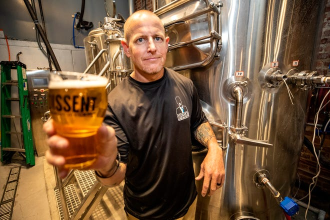 Chris Price , owner of Dissent Craft Brewing with their Dissent IPA beer in Lakeland Fl. Thursday Oct. 7 2021. Dissent Craft Brewing out of St. Pete is opening a new brewery location next to Pita Pit downtown. The brewery and tap room will offer a wide variety of taps and outdoor seating for customers.