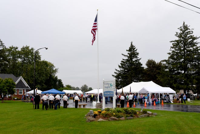The large American Flag flies for the first time on the 43-foot pole outside the Visiting Angels building in Monroe after the memorial dedication took place Thursday.