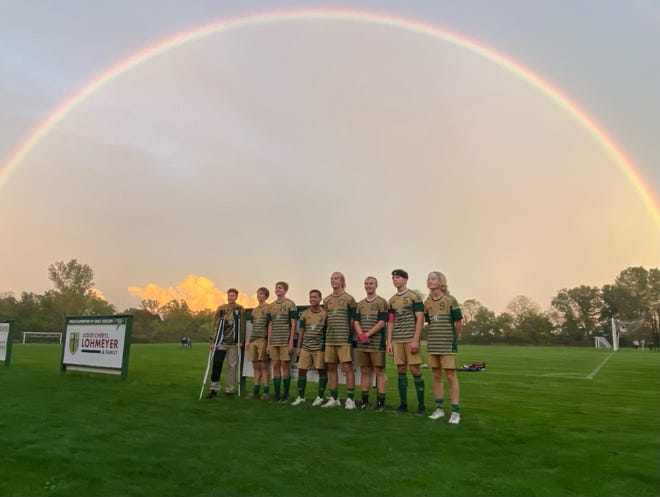 The seniors for St. Mary Catholic Central's soccer team come together under a rainbow after the Falcons defeated Gibraltar Carlson 6-3 Thursday.