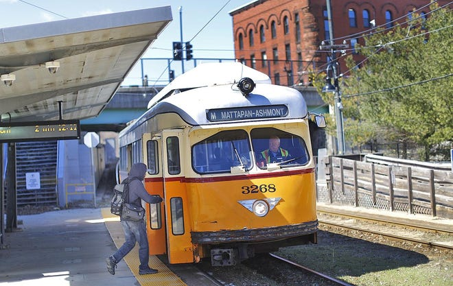 A commuter gets on a Mattapan Line trolley at the  Milton Village stop.