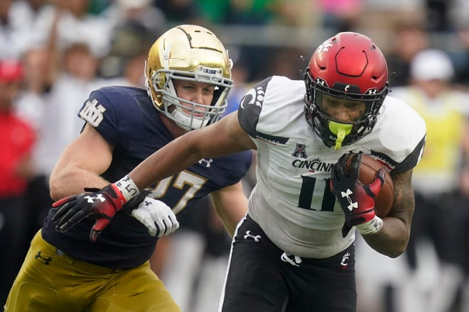 Cincinnati's Leonard Taylor, right, is chased by Notre Dame's JD Bertrand during last Saturday's game in South Bend, Ind. The Bearcats won, 24-13.