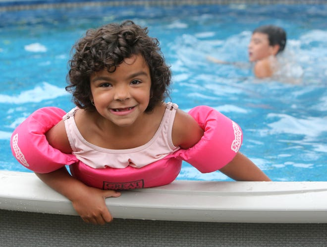 Dallas Hollis enjoys her new pool at her home in Alliance on Thursday, Oct. 7, 2021. In the background is her brother Chandler Hollis. The seven-year-old girl, who was diagnosed with a Wilms tumor in 2020, is now cancer-free and had a pool built in her backyard through Make-A-Wish.