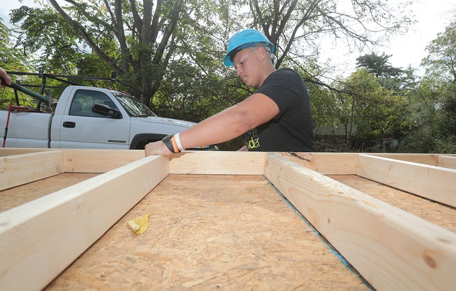 Washington High School Jaiden Woods nails a wall support last week at the Habitat for Humanity home that he and his classmates are working on.