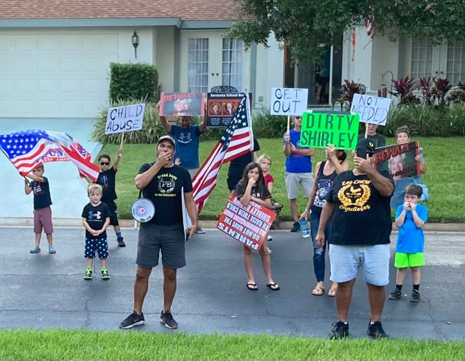 Adults and children protest Oct. 4 outside the home of Sarasota County School Board Chairwoman Shirley Brown. They called for her resignation.