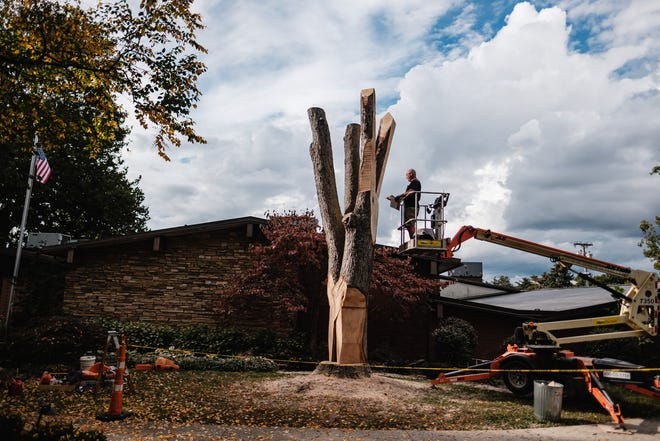 Dan Warther works to carve seven giant pairs of pliers from a maple tree in front of the Ernest Warther Museum & Gardens in Dover on Friday.