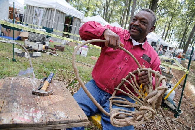 Andrew McCall bends vines to form a basket as he creates crafts at the Kentuck Festival of the Arts in Kentuck Park in this 2017 file photo. McCall said he uses wisteria and kudzu vines to make his creations. This year's festival is scheduled for Oct. 16-17.[Staff Photo/Gary Cosby Jr.]