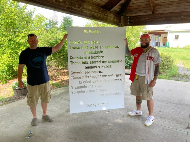 """Elijah Johnson, left, and Danny Fantom display a stencil of Fantom's poem for the WCPA's """"A Walk in the Woo"""" project."""