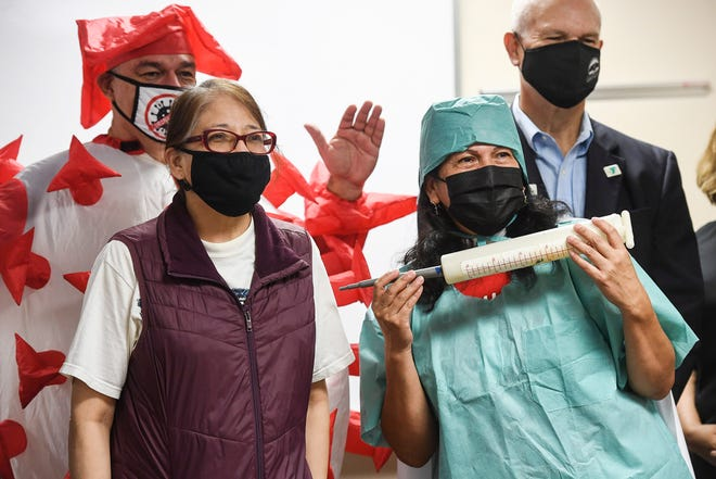 Rosendo Lopez and Linda Miller dressed as COVID-19 and a nurse during a booster shot clinic with the Mexican Consulate October 8, 2021.