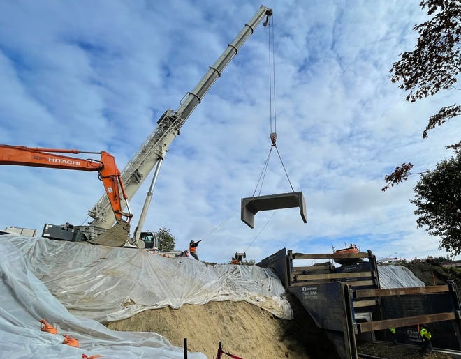A crane Friday hoists a 26-ton concrete lid into Ostrich Bay Creek, where it passes under Kitsap Way. The city is replacing an aging and deficient culvert there for $1.7 million.