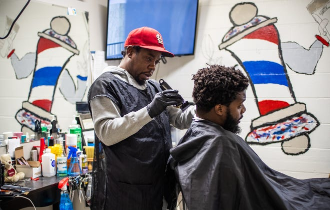 Tommy Dotson trims the hair of customer Fred Harris  inside his barbershop, T.E.DÕZ Barbershop, on Indianapolis' south side Friday, Oct. 8, 2021. Dotson used $15,000 of his savings, money left to him by his mother, to repair the old building and opened in February 2020, One month later COVID-19 forced him to shut down. This was one of a series of obstacles Dotson has faced along the way to opening the shop, but despite the obstacles, he remains optimistic.
