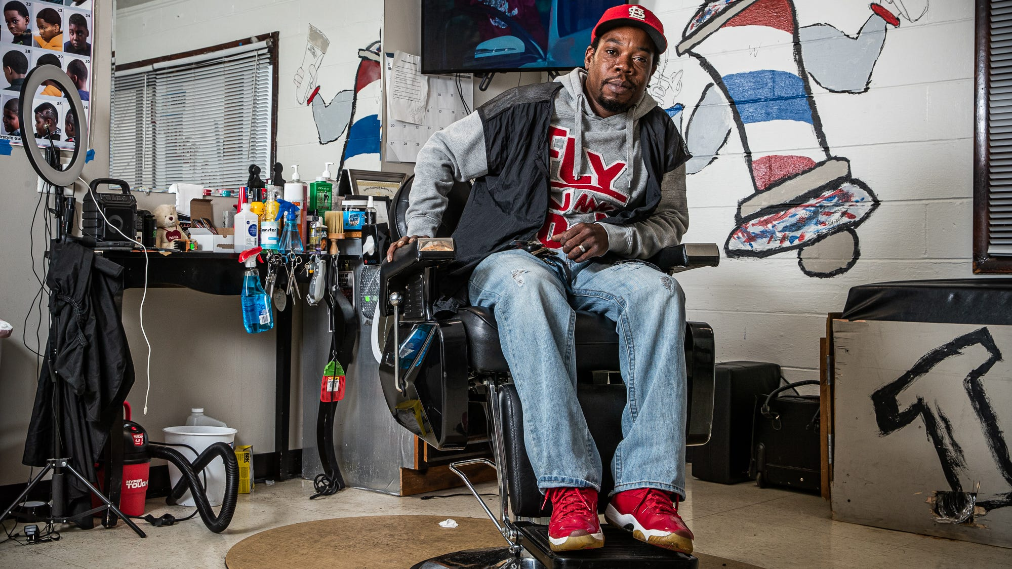 Tommy Dotson waits for his first customer of the day inside his barbershop, T.E.DÕZ Barbershop, in Indianapolis' Mars Hill neighborhood Friday, Oct. 8, 2021. Dotson used $15,000 of his savings, money left to him by his mother, to repair the old building and opened in February 2020. One month later, COVID-19 forced him to shut down. This was one of a series of obstacles Dotson has faced along the way to opening the shop. Despite the obstacles, he remains optimistic.