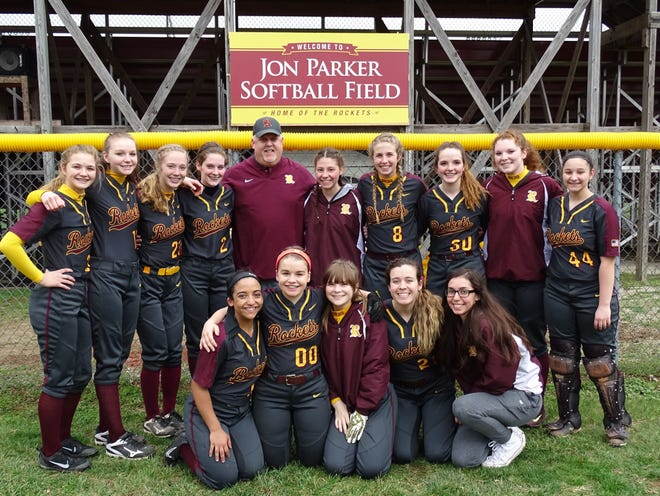 Berne Union softball coach Jon Parker stands with his team and in front of sign bearing his name after the softball field was renamed in his honor in 2017. After 26 seasons, Parker stepped down as the Rockets head coach.