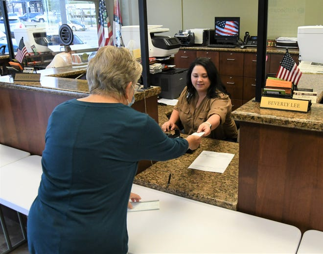 Baxter County deputy collector Jennifer Zappa (seated) accepts a check from Lana Pate of Mountain Home on Friday morning. Baxter County residents have until Friday to pay their 2020 property taxes or incur a late penalty.