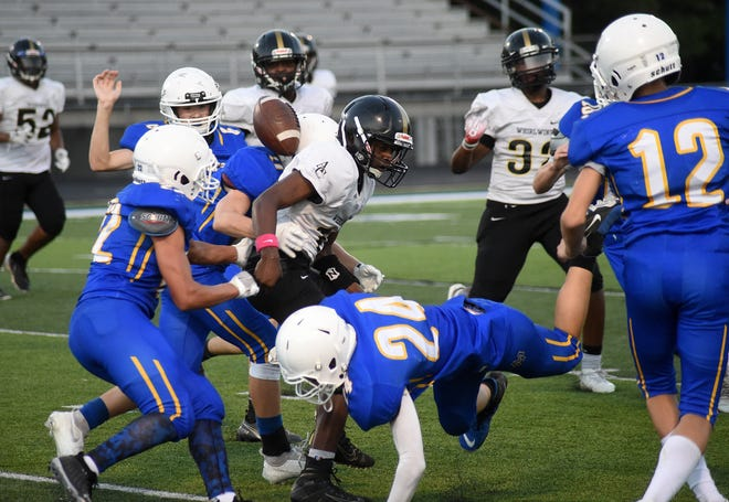 Players scramble for the football after Mountain Home's Isaac Wiggins (24) forced Annie Camp's Jamarion Nelson to fumble on a kickoff return late in the first half of the Junior Bombers' 33-12 victory Thursday night at Bomber Stadium.