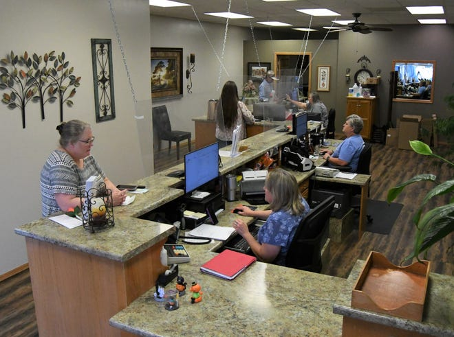 Deputy assessors help a trio of visitors to the Baxter County Assessor's Office on Friday morning. About 160 county employees will receive federally funded premium pay for working through the COVID-19 pandemic last year.