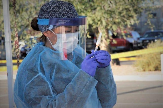Heather Boitano prepares a vaccine Oct. 31, 2020, during a free flu shot clinic at the San Juan Regional Medical Center in Farmington.