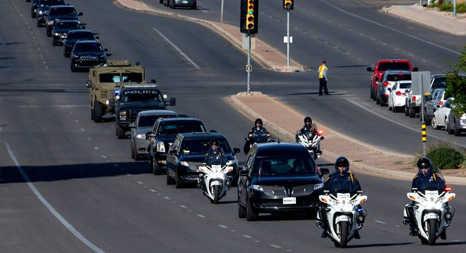 After departing from Bring's Broadway Chapel, a hearse and law enforcement procession for Drug Enforcement Administration Supervisory Special Agent Michael G. Garbo travels down E. Broadway Blvd. in Tucson on Oct. 8, 2021.