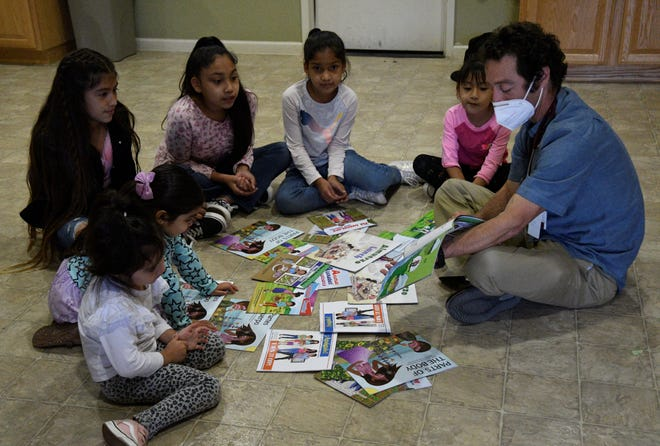 Family physician Joshua Deutsch reads his health books to a group of young girls.