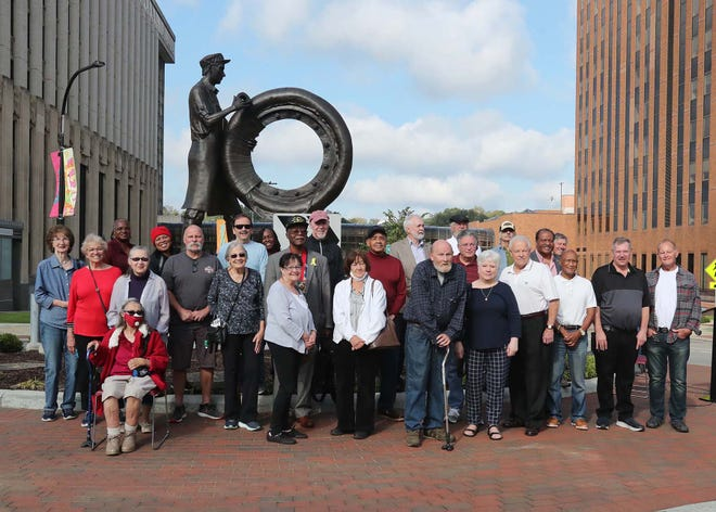 Former workers in the rubber industry in Akron pose in front of the statue after a public dedication of the Rubber Worker Statue and Akron Stories Project on Saturday downtown.